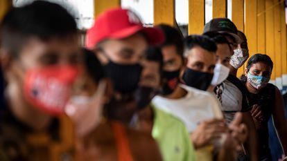 Pessoas fazem fila para votar no único centro eleitoral da comunidade Lago do Catalão, na zona rural de Iranduba, no Amazonas. No Lago do Catalão, onde todas as casas ficam na água, os eleitores vão de barco para votar na escola da comunidade.