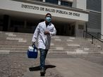 A health worker walks outside Chile's Public Health Institute in Santiago, Chile, Wednesday, Dec. 16, 2020. The institute announced on Wednesday its authorization of the Pfizer vaccine against COVID-19, which will be voluntary and free, and is planned to start in 2021. (AP Photo/Esteban Felix)