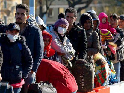 Dezenas de refugiados, neste domingo, na fronteira da Áustria com a Alemanha.