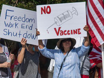 Um grupo contrário às medidas de confinamento se manifesta na Califórnia com um cartaz crítico às vacinas.