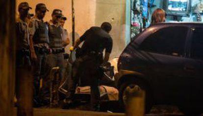 Policiais recolhem corpo de vítima de chacina no Campo Limpo.