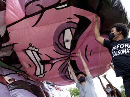 Manifestantes inflam boneco que representa o presidente Jair Bolsonaro, em 21 de fevereiro em Brasília.