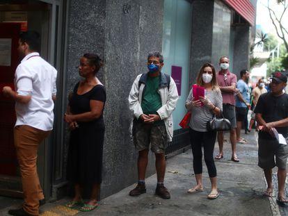 As pessoas esperam na fila para entrar em um banco durante o surto da doença por coronavírus, no bairro de Copacabana, no Rio de Janeiro.