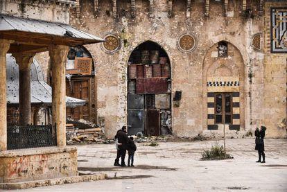 Hamid Kenefati, morador de Aleppo, tira uma foto junto à família na Mesquita de Omeya, depois do fim dos combates.