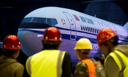 Grupo de trabalhadores diante de um Boeing 737 Max 8 da Air China, em uma imagem de arquivo. Em vídeo, morrem os 157 ocupantes da aeronave acidentada.