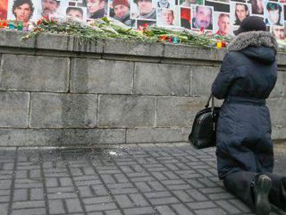 Uma mulher homenageia os mortos durante os protestos que derrubaram o presidente ucraniano, Víctor Yanukóvich.