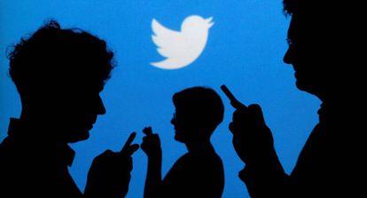 Usuários de celulares em frente ao logotipo do Twitter.