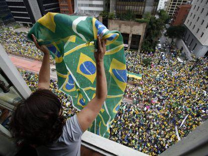 Mulher agita bandeira para manifestantes.