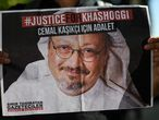 (FILES) In this file photo taken on October 02, 2020, friends of murdered Saudi journalist Jamal Khashoggi hold posters bearing his picture as they attend an event marking the second-year anniversary of his assassination in front of Saudi Arabia Istanbul Consulate. - The US director of national intelligence is expected to release a damning report on February 26, 2021, that fingers Saudi Crown Prince Mohammed bin Salman for the brutal murder and dismemberment of dissident journalist Jamal Khashoggi in October 2018. The classified report is believed to say that, based on intelligence collected by the CIA and other spy bodies, the kingdom's de facto leader directed the assassination of the respected US-based writer in the Saudi consulate in Istanbul. (Photo by Ozan KOSE / AFP)