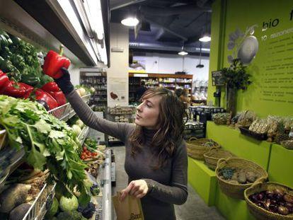 Uma mulher compra vegetais ecológicos.