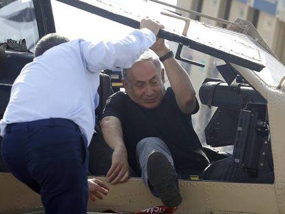 Primeiro-ministro de Israel, Benjamin Netanyahu, sai de um helicóptero ajudado por comandante da força aérea de Israel.