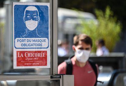 Homem caminha próximo a aviso de obrigatoriedade do uso de máscaras el locais fechados em Lille, no norte da França.