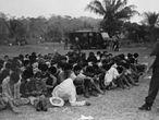 Posseiros rendidos reunidos no campo de futebol do acampamento.
