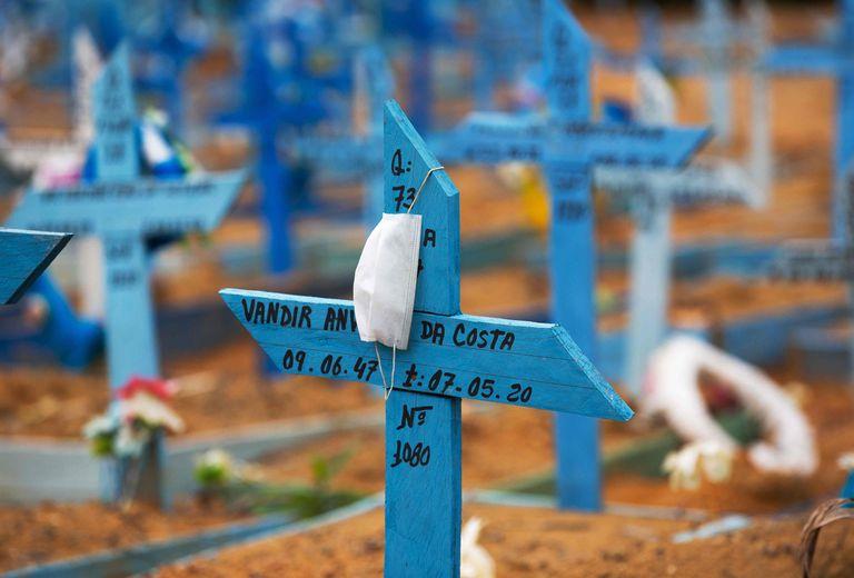 Uma máscara facial é colocada em uma cruz em uma área reservada para o sepultamento das vítimas da Covid-19 no cemitério Nossa Senhora Aparecida em Manaus.