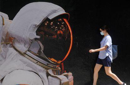 Mulher com máscara de proteção passa por muro pintado em Hong Kong, onde ocorreu caso de reinfecção por covid-19.
