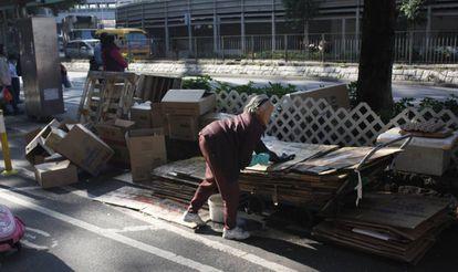 Mulher coletando papelão no bairro de Sheung Shui.