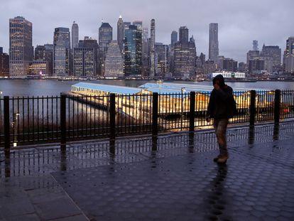 Homem caminha por uma rua deserta diante dos prédios de Manhattan.