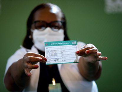 A enfermeira Mônica Calazans, primeira pessoa vacinada no Brasil, exibe sua caderneta de imunização.