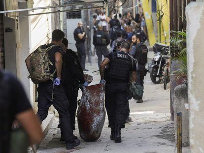 Policiais civis carregam o corpo de uma pessoa morta durante operação na favela do Jacarezinho, nesta quinta-feira, 6 de maio, no Rio de Janeiro.