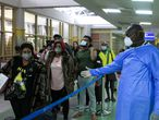 Nairobi (Kenya), 29/01/2020.- A Kenyan health worker (R) guides passengers to a health screening after they arrived from China, at Jomo Kenyatta International Airport in Nairobi, Kenya, 29 January 2020. African airports are on high alert after a suspected cases of cononavirus were detected in the Ivory Coast, Kenya and Ethiopia. (Costa de Marfil, Etiopía, Kenia) EFE/EPA/DANIEL IRUNGU
