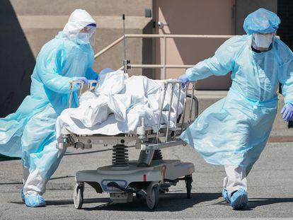 Trabalhadores transportam um corpo no hospital Wyckoff, em Nova York, em abril.