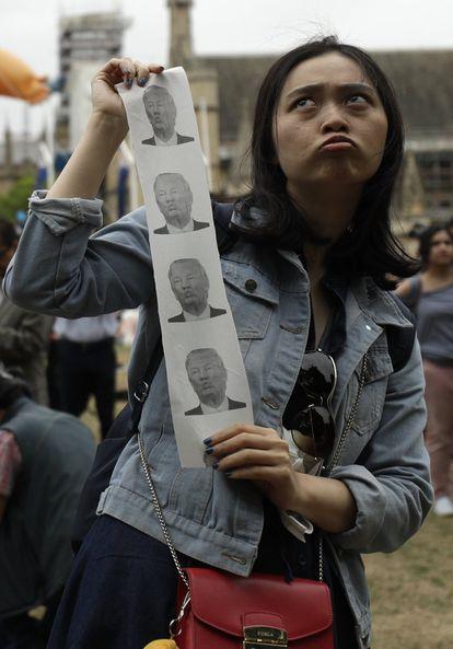 Uma mulher posa com fotografias do presidente Donald Trump em Londres