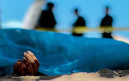 Peritos criminais observam o corpo de um homem morto em Acapulco em 2016.