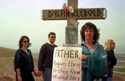"""Pessoas visitando o ponto no qual foi feita uma homenagem às vítimas do massacre de Columbine, em Littleton, Colorado. Na imagem, una cruz com a foto e o nome de Dylan Klebold e um cartaz no qual se lê: """"Pai, perdoai-os porque eles não sabem o que fazem"""" (Jesus)."""