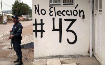 Policial em Guerrero (México) ao lado de pichação pelo boicote eleitoral.