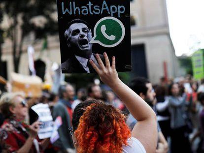 Uma mulher segura um cartaz, durante um protesto em São Paulo, contra suposto disparo em massa de notícias falsas em favor de Jair Bolsonaro.