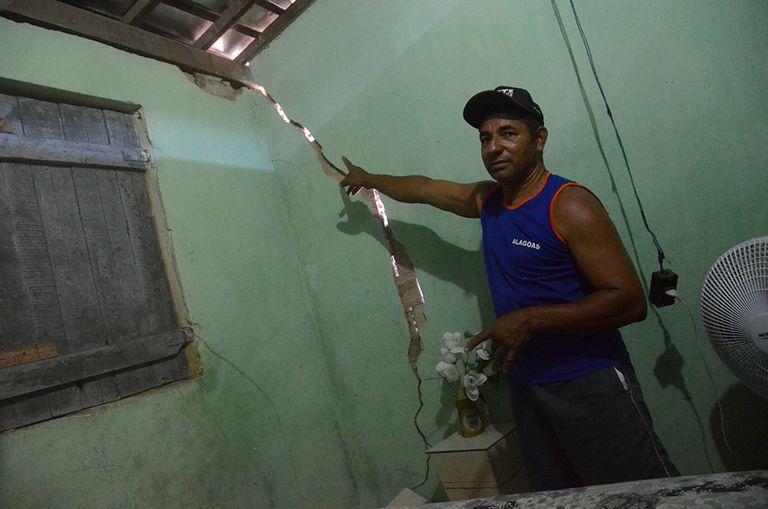 Jânio exibe as paredes rachadas de sua casa.