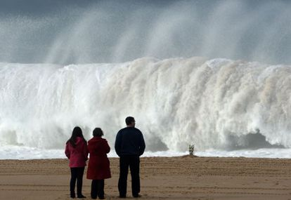 Três pessoas observam uma onda na praia do Meco, onde ocorreu a tragédia.