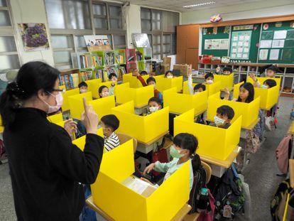 Alunos de uma escola em Taipei (Taiwan) usam máscaras e são separados por divisórias para prevenção do Covid-19.