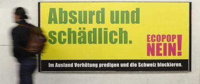 Um cidadão de Zúrich passa por adiante de um cartaz contrário à iniciativa de Ecopop para frear a imigração.
