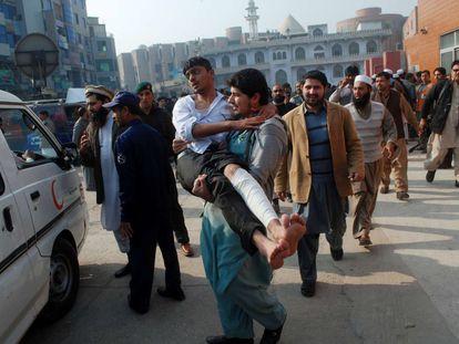 """Vítima do ataque é resgatada. O porta-voz talibã Mohamed Jorasani afirmou a France Presse que os milicianos receberam ordens de disparar contra """"os estudantes mais velhos, mas não contra as crianças""""."""