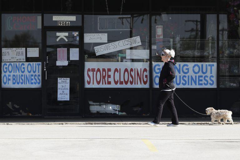 Mulher passa diante de vitrine de uma loja fechada, na quarta-feira, em Niles (Illinois).