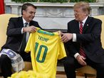 El presidente brasileño, Jair Bolsonaro, entrega a su homólogo estadounidense Donald Trump, una camiseta de fútbol de la selección nacional brasileña con su nombre, en el Despacho Oval de la Casa Blanca, el 19 de marzo de 2019.