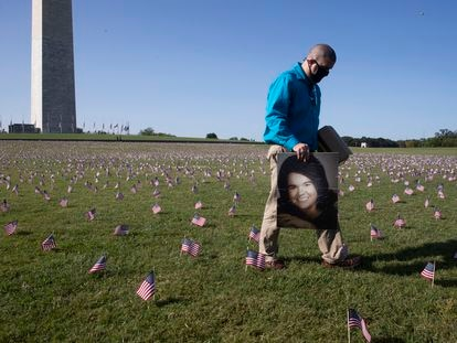 Um homem passa com um retrato de sua mãe, que morreu de covid-19, entre as milhares de bandeiras colocadas ao lado da base do obelisco de Washington em homenagem às vítimas do novo coronavírus, no dia 22 de setembro.