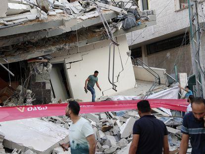 Palestinos vistoriam os escombros de um edifício residencial destruído por um ataque aéreo israelense na Faixa de Gaza.