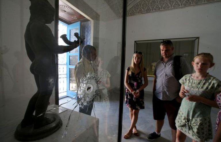 Uma família contempla, na terça-feira no Museu Nacional do Bardo, uma obra baleada durante o atentado islâmico de março passado.