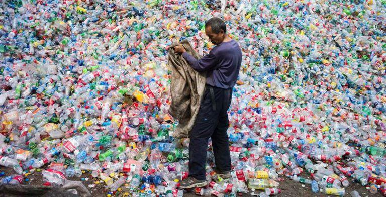 Trabalhador classifica garrafas de plástico para reciclar em Pequim.