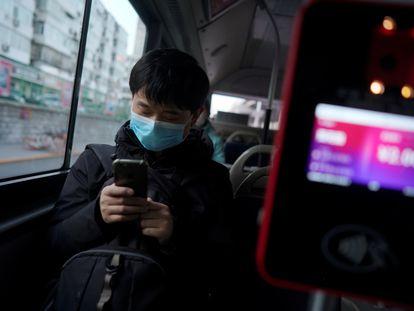 Passageiro de ônibus olha o celular em Pequim.