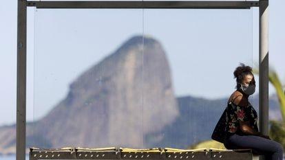 Mulher com máscara de proteção sentada em ponto de ônibus em Niterói, com o Pão de Açúcar no fundo.