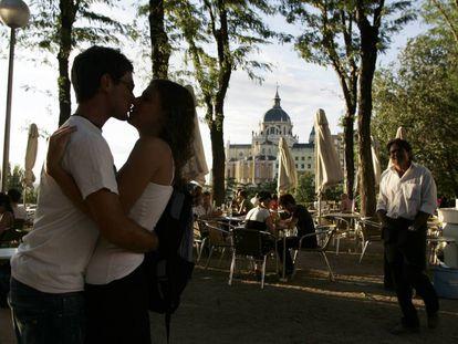 Jovens beijam-se em Madri com a Catedral de Almudena ao fundo.