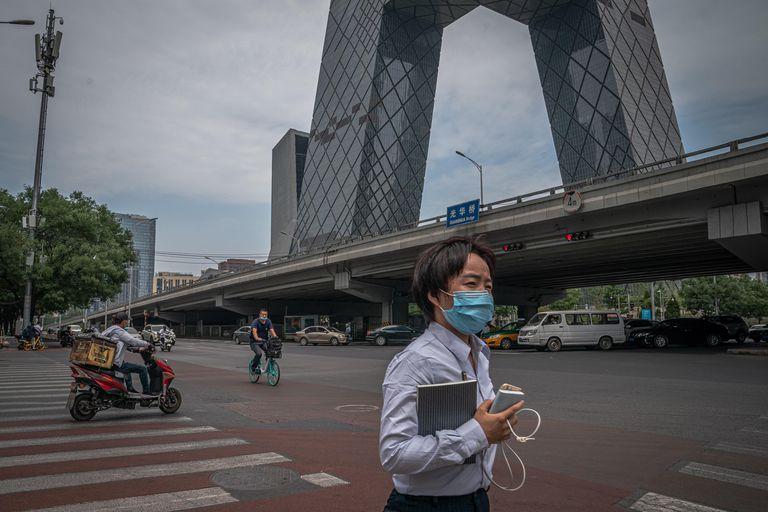 Uma mulher com máscara passa em frente à sede CCTV, a televisão estatal chinesa, um dos edifícios mais emblemáticos de Pequim.