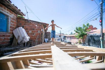 Neto do pescador Antônio Banqueiro caminha sobre o esqueleto da jangada que está sendo construída pelo avô no morro Santa Terezinha.