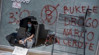 Uma manifestante dentro de um caixa de bitcoins destruído durante os protestos de quarta-feira.
