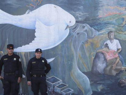 Policiais salvadorenhos diante de um mural que faz alusão à guerra civil de El Salvador (1980-92).