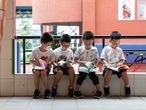 This photo taken on September 1, 2020 shows elementary school students reading books on the first day of the new semester in Wuhan in China's central Hubei province. - Students in face masks returned to class on September 1 in Wuhan, the central Chinese city where the coronavirus first emerged last year, as the city opened schools and kindergartens for the first time in seven months. (Photo by STR / AFP) / China OUT