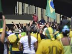 Brazil's President Jair Bolsonaro, center, speaks to supporters during a protest in front the army's headquarters during the Army day, amid the new coronavirus pandemic, in Brasilia, Brazil, Sunday, April 19, 2020. Bolsonaro came out in support of a small protest Sunday that defended military intervention, infringing his own ministry's recommendations to maintain social distancing and prompting fierce critics. (AP Photo/Andre Borges)